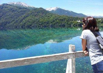 mulher observa um lago espelhado